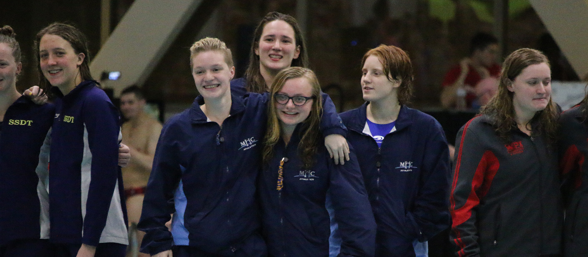 Photo showing the Lyons swimming & diving 800-freestyle relay team from the first night of action at the NEWMAC Championships. Left to right: Claire Beckett, Naomi Brown, Ashton Bliss and Bri Groves.