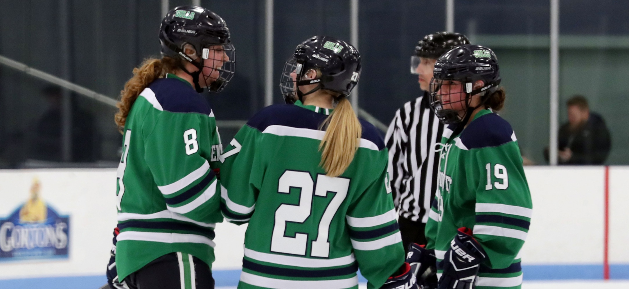 Ellen Carter, Nicole Demers, and Jade Meier talk during a stop in play.