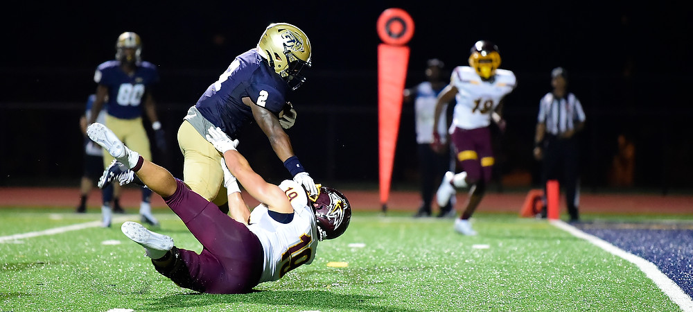 RJ Randle runs over an Alvernia defender as he scores a touchdown for the Gallaudet Bison during its night game at Hotchkiss Field.