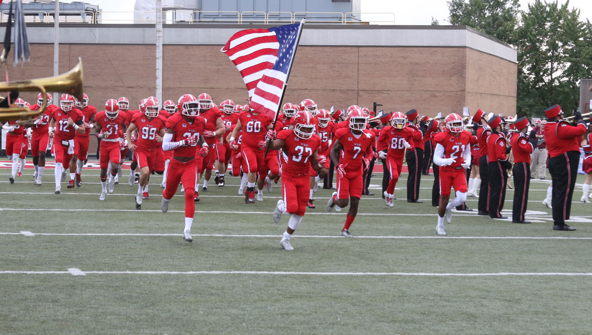 Members of the YSU Football team run on the field.