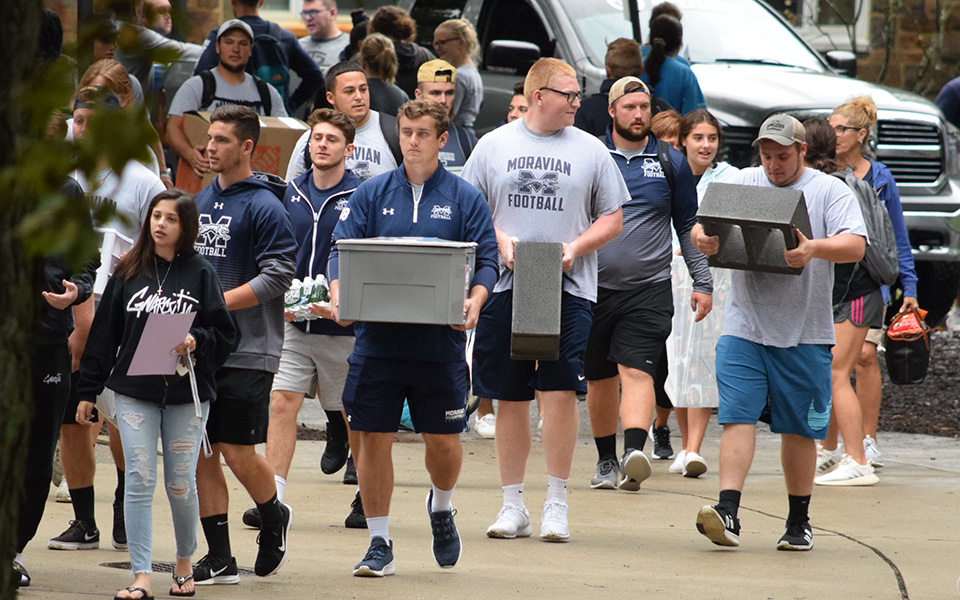 Members of the Moravian football team help unload vehicles during Freshman Move In day.