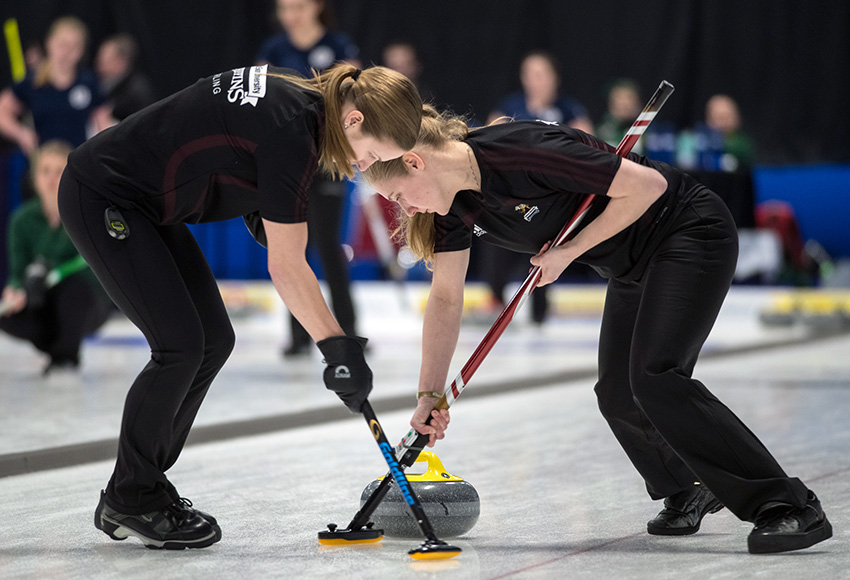 Andie Kurjata, left, and Taitan Hagglund sweep a rock during round robin action at the CCAA nationals (CCAA photo).