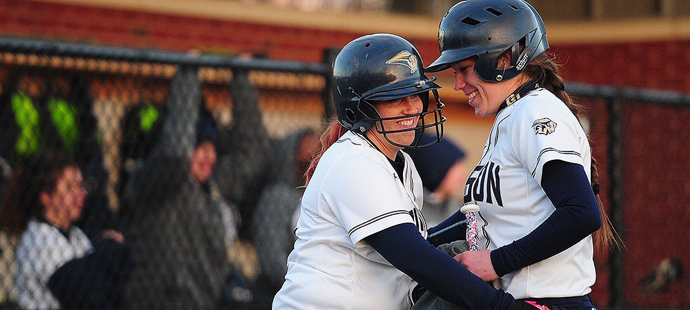 Gallaudet softball players Alyssa Barlow (left) and Kelsey Hudson (right) shake hands at home plate.