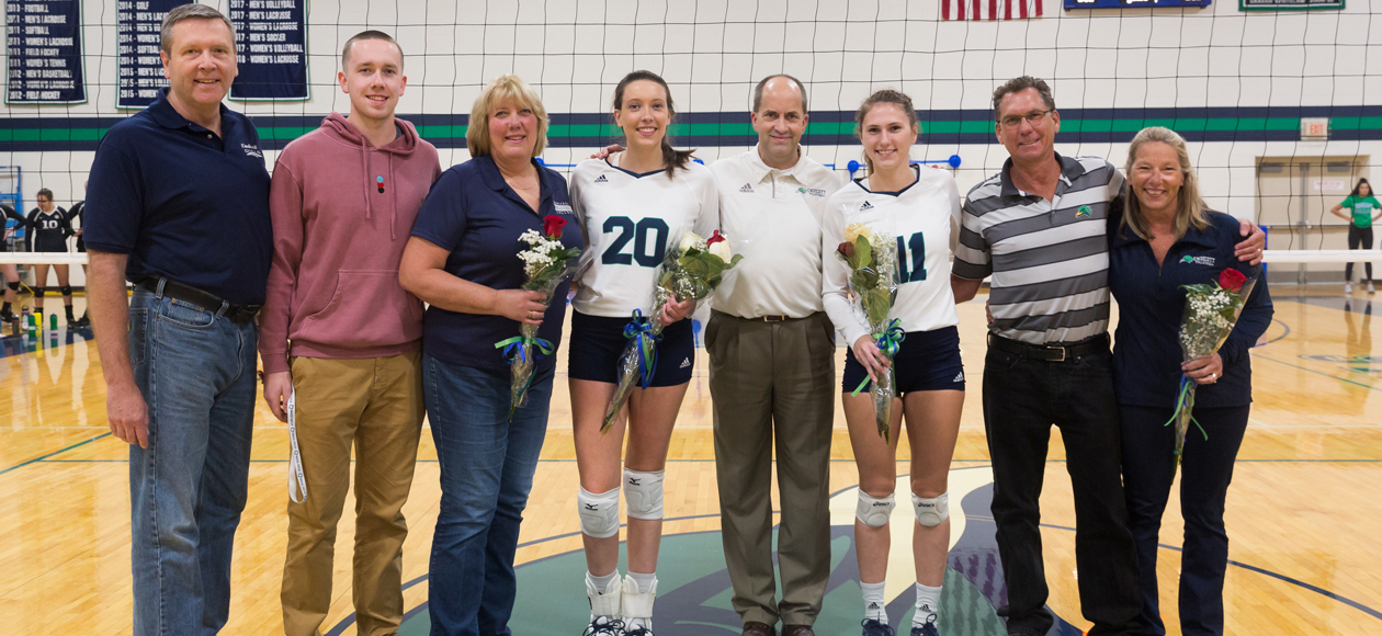 Image of seniors Emily Diezmann and Emma Mancini posing at the net with head coach Tim Byram and their families.