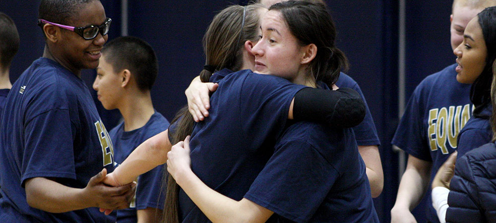 Gallaudet seniors Kelsey Hudson (left) and Lawjen Ashmore (right) hug prior to the start of the Bison basketball game on Senior Day.