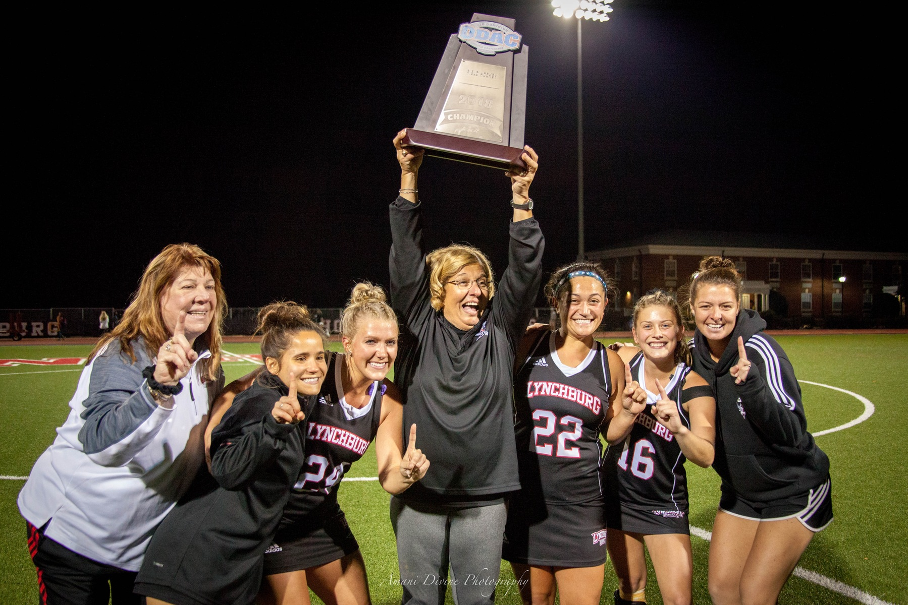 Field hockey players and coaches hoist the ODAC championship trophy