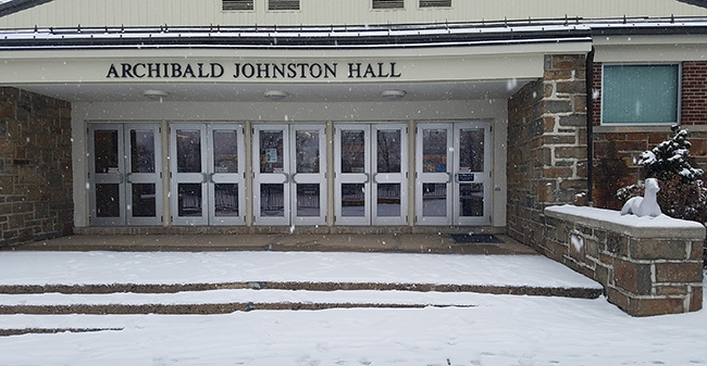 The snow is falling outside Johnston Hall.