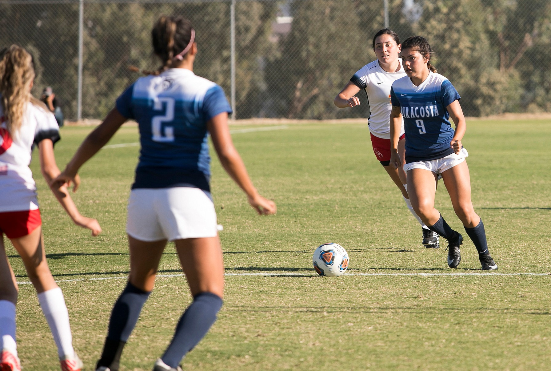 MiraCosta soccer player passes to teammate.