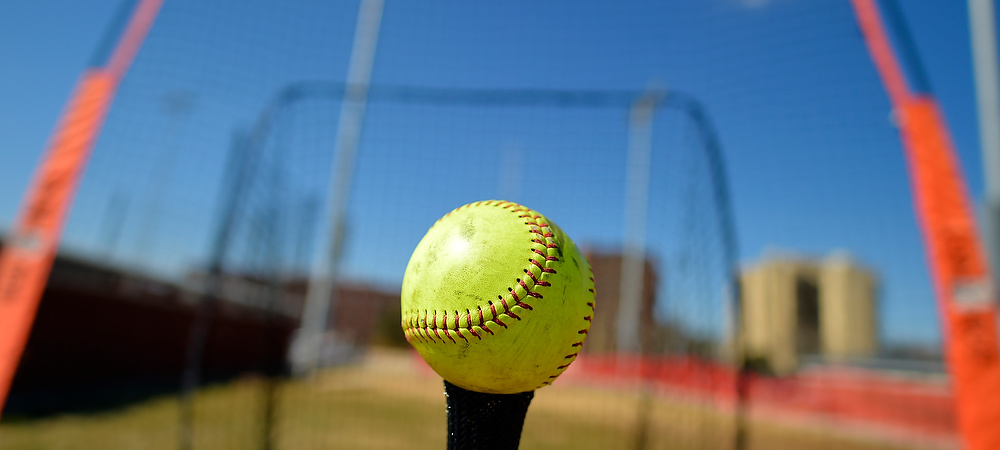 On a sunny day a softball sits on the tee and in the backround is a bright orange and black softball net.