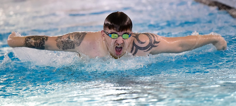 GU men's swimmer Barry McGrain III does a butterfly stroke in the swimming pool. He is wearing goggles and takes a breath as he swims.