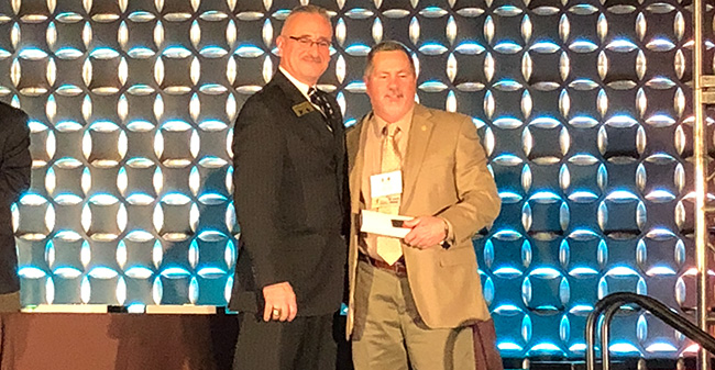 Head Athletic Trainer Bob Ward (right) poses on stage while being inducted into the Eastern Athletic Trainers Association Hall of Fame.