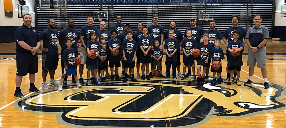 Participants in the Gallaudet men's basketball Parent & Son Basketball Clinic held at GU on June 3, 2018. Group photo at mid-court on the GU Bison logo.