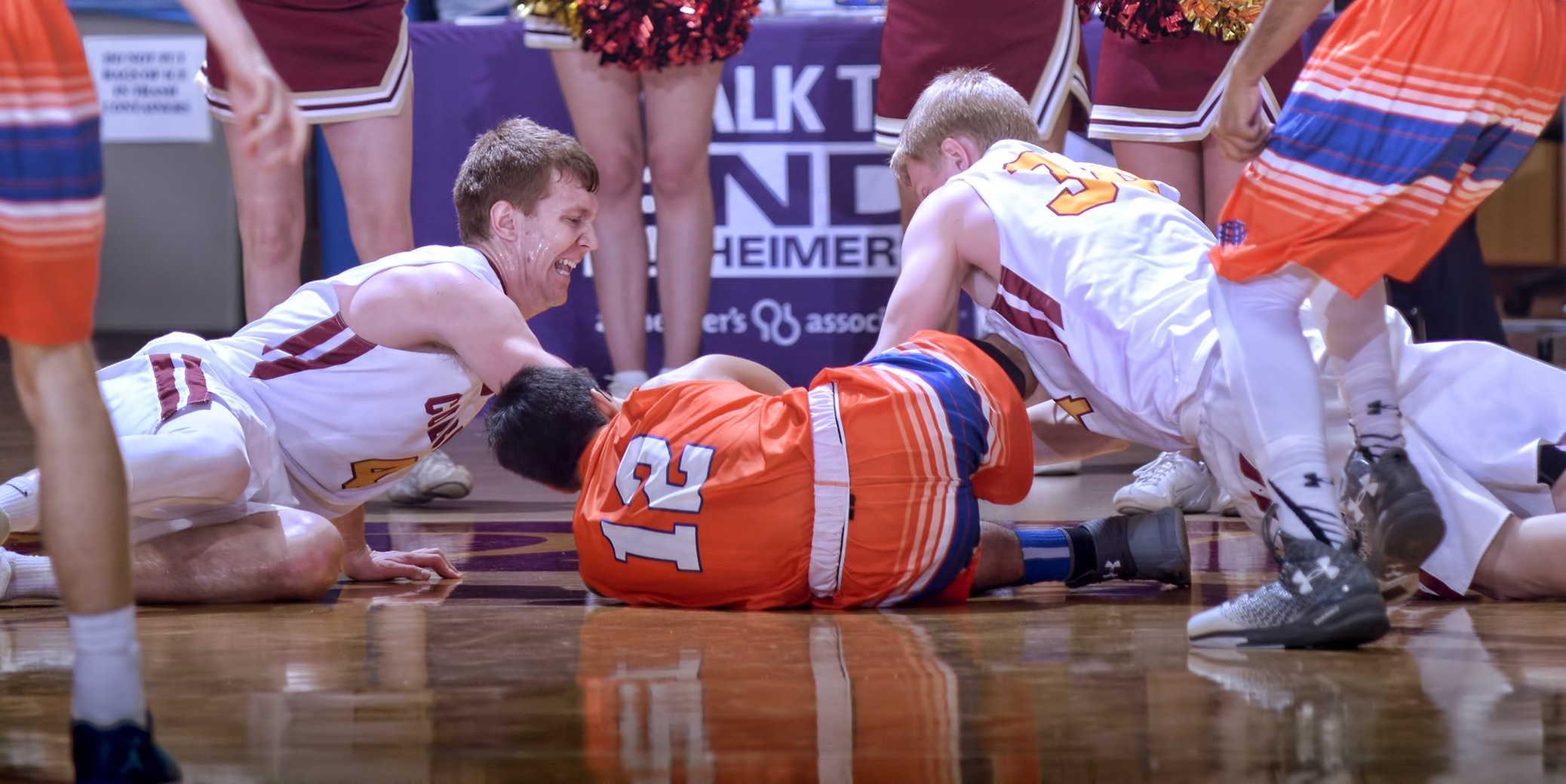 Collin Larson (L) and Andrew Hoeln dive on the floor for a loose ball during the Cobbers 100-81 win over Macalester.