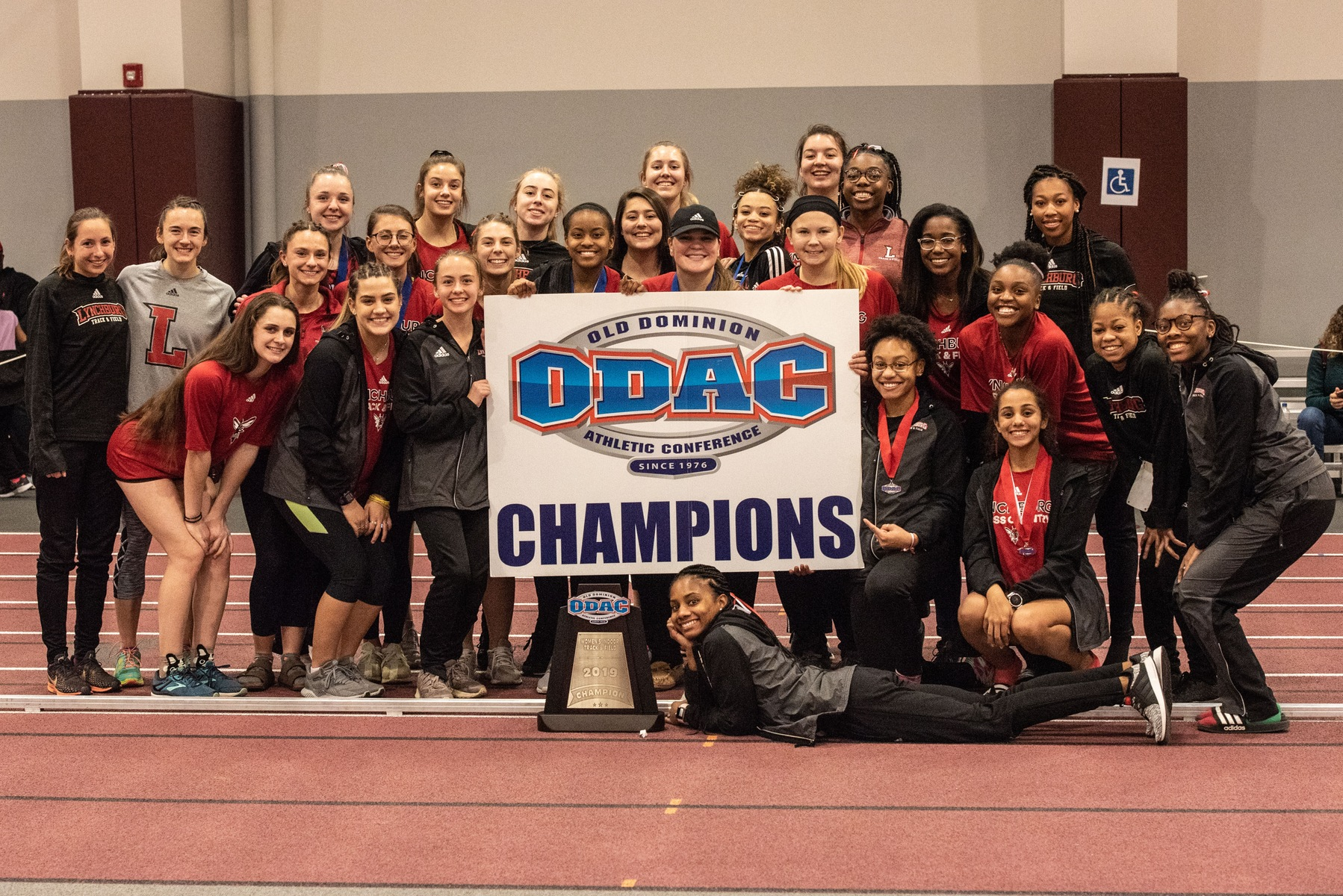 Lynchburg women's track poses with ODAC champions sign and trophy