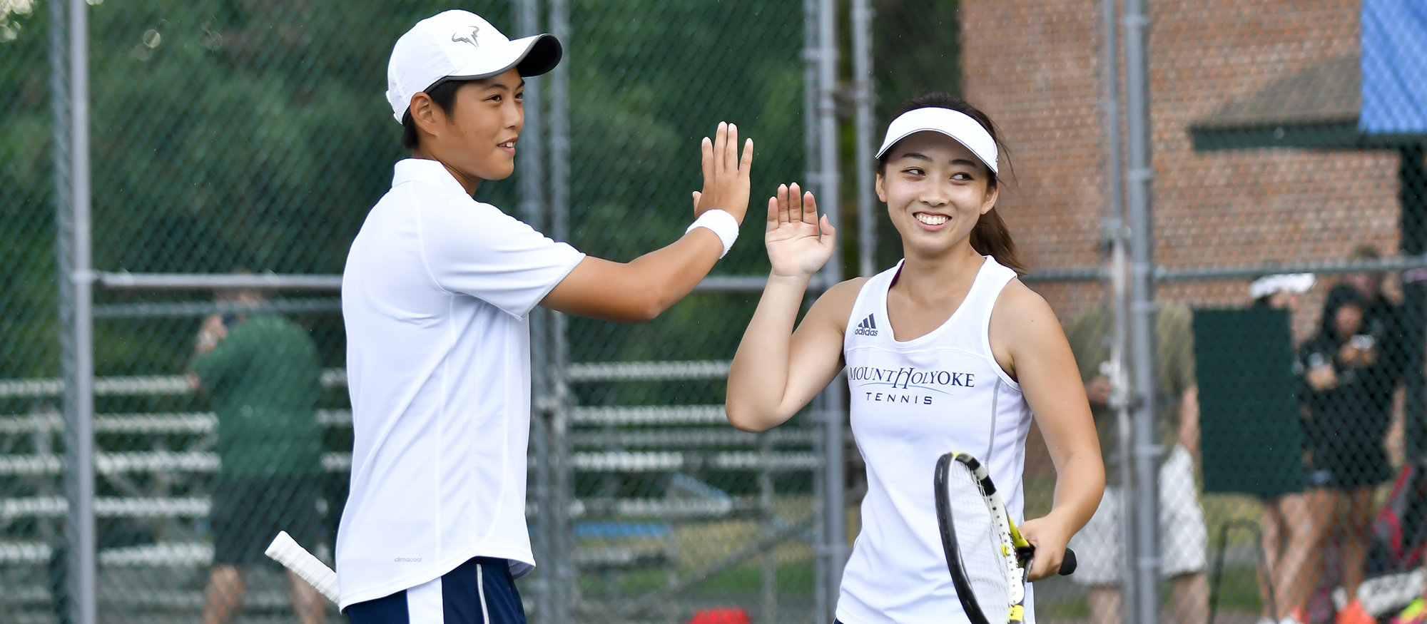 Action photo of Lyons tennis players Ching-Ching Huang (left) and Ayame Yazawa (right).