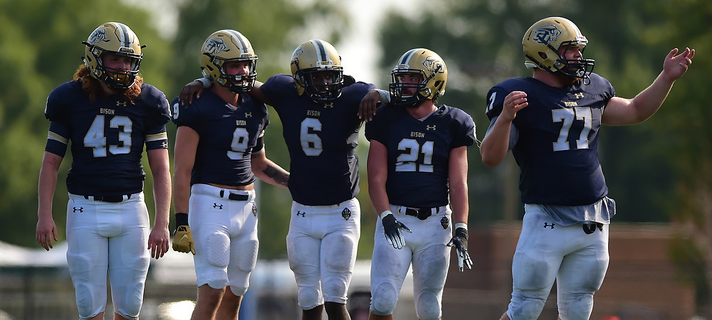 Gallaudet's starting defenders on the football team line up together during a day game.