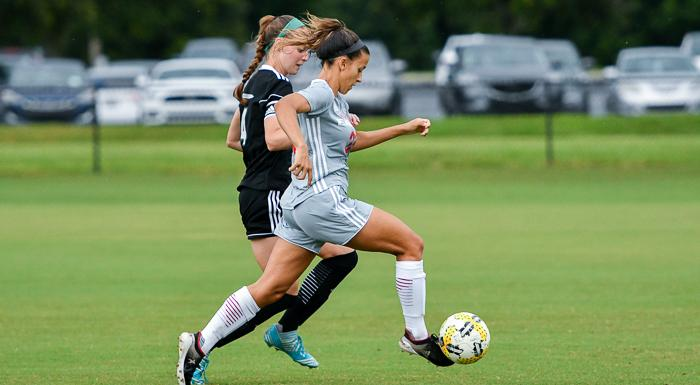 Madison Politis dribbles past a Webber defender. The sophomore scored twice to give the Eagles a 2-0 win in their first game of the regular season. (Photo by Tom Hagerty, Polk State.)