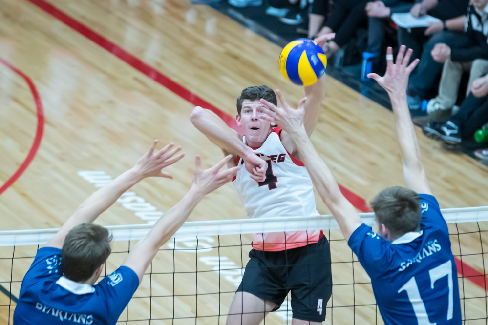 Daniel Thiessen swings against a Trinity Western block during the Wesmen's loss Saturday, November 10, 2018. (Kelly Morton/Wesmen Athletics)
