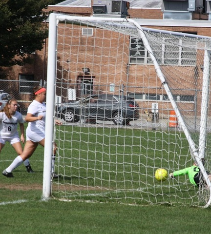 Two Broome players at net scoring goal