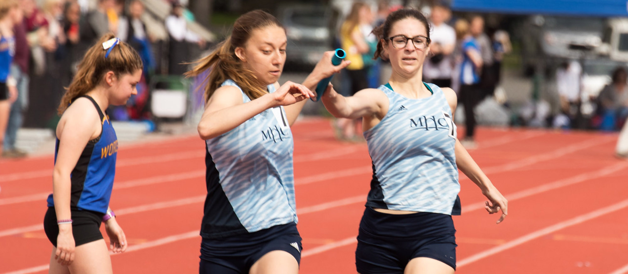 Action photo of seniors Corrin Moss and Emsie Cronin passing the baton in the 4x800 relay. Photo courtesy of J. Cronin - outrageousphotography.net