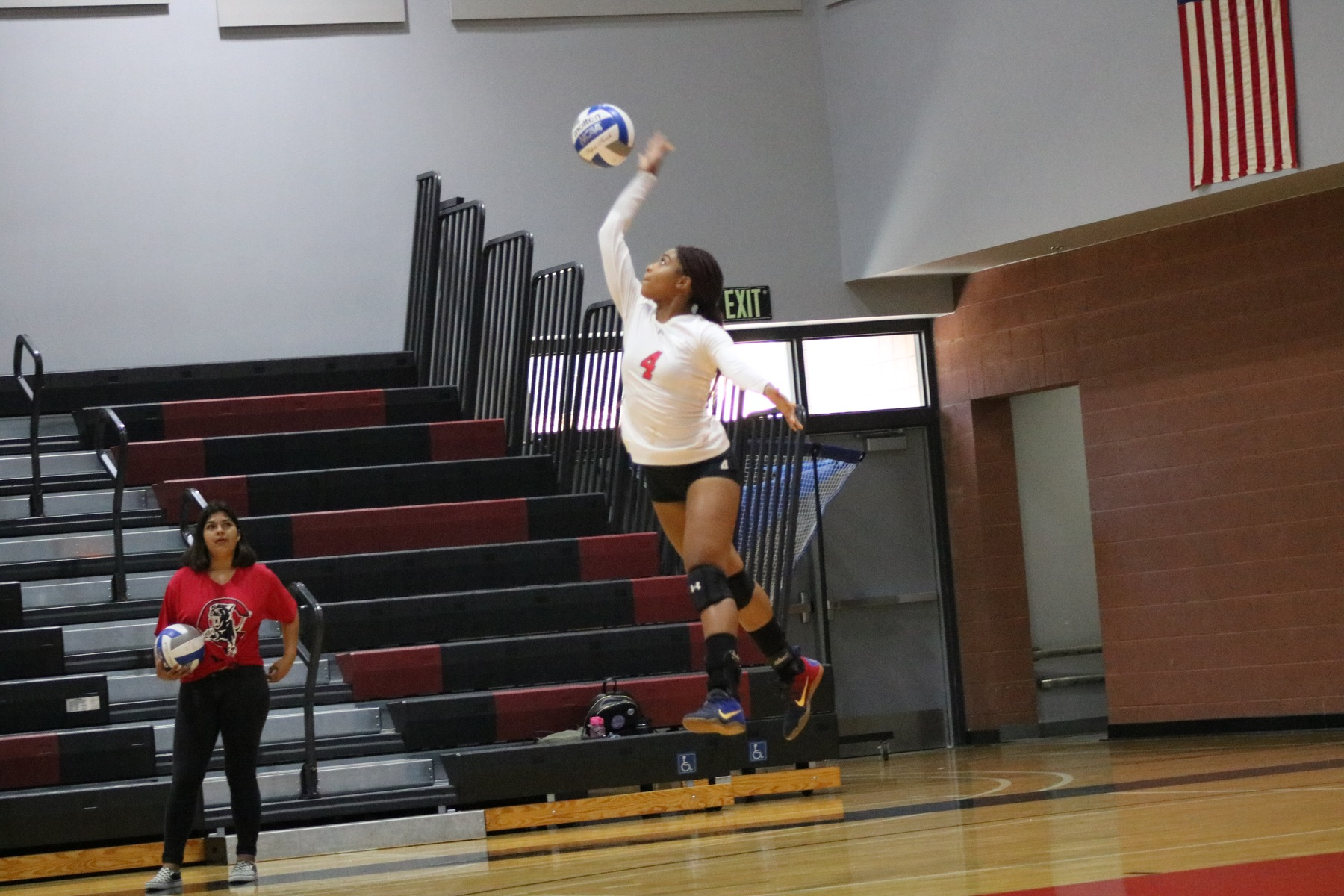 Women's volleyball player serves ball