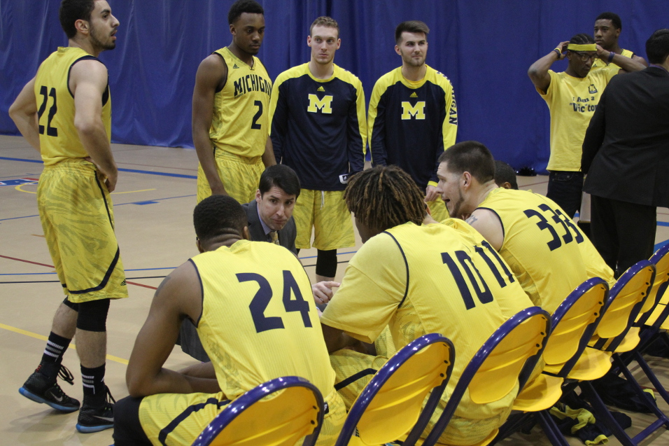 The men's basketball team huddles around Head Coach Taylor Langley