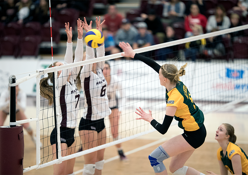Kate Rozendaal and Haley Gilfillan post a block against Alberta on Saturday night. The Griffins came close to winning the rematch on Sunday but fell short in the fifth set (Robert Antoniuk photo).