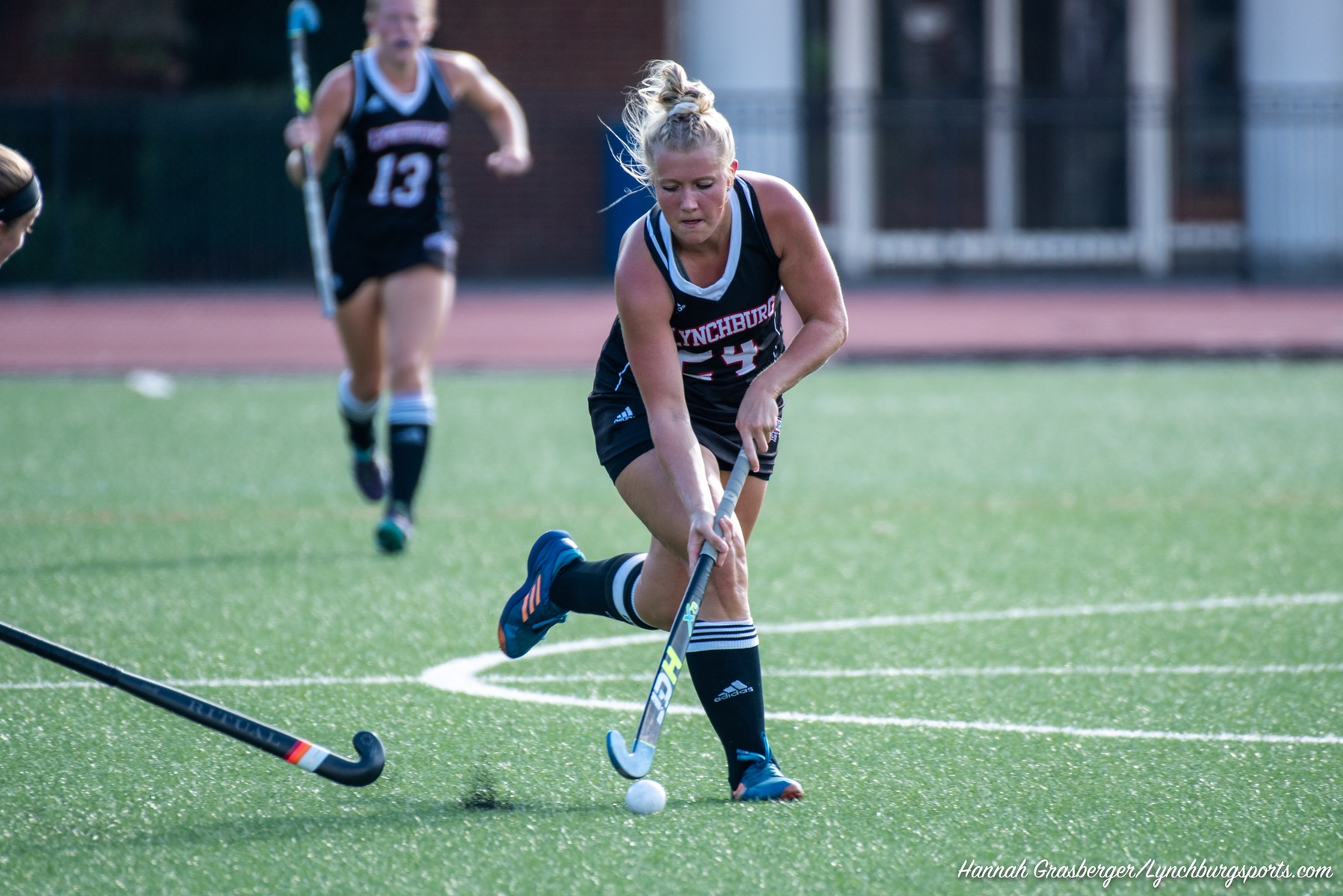 Kayla Copeman hitting a field hockey ball in a game.