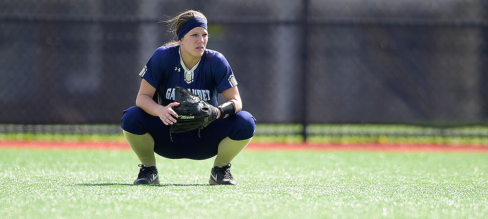 Gallaudet outfielder Kelsey Hudson crouches down in the outfield during a pitching change.