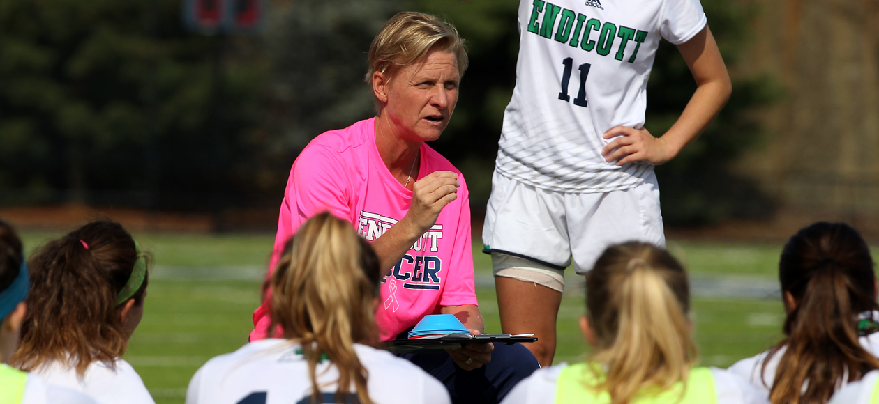 Image of head coach Jodi Kenyon speaking to the team at half time.