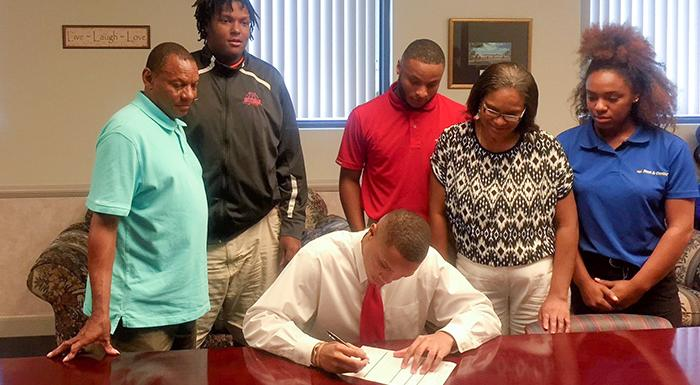 Surrounded by his family, Kadeem Webb signs letter of intent to play basketball for the Eagles.