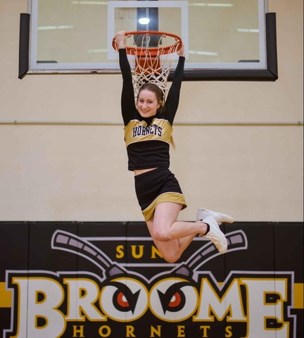 Cheerleader holding on to basketball rim