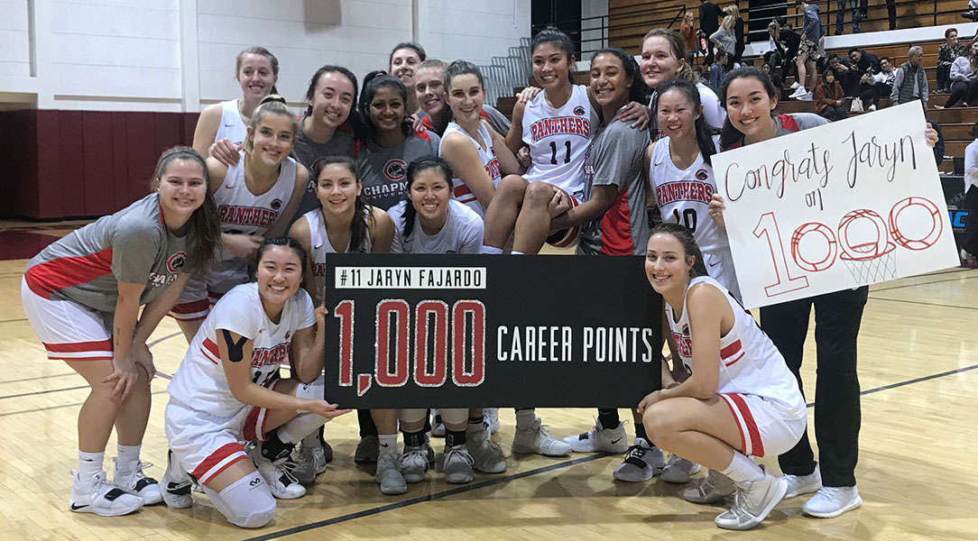 The women's basketball team poses with Jaryn Fajardo to celebrate scoring her 1,000th point.