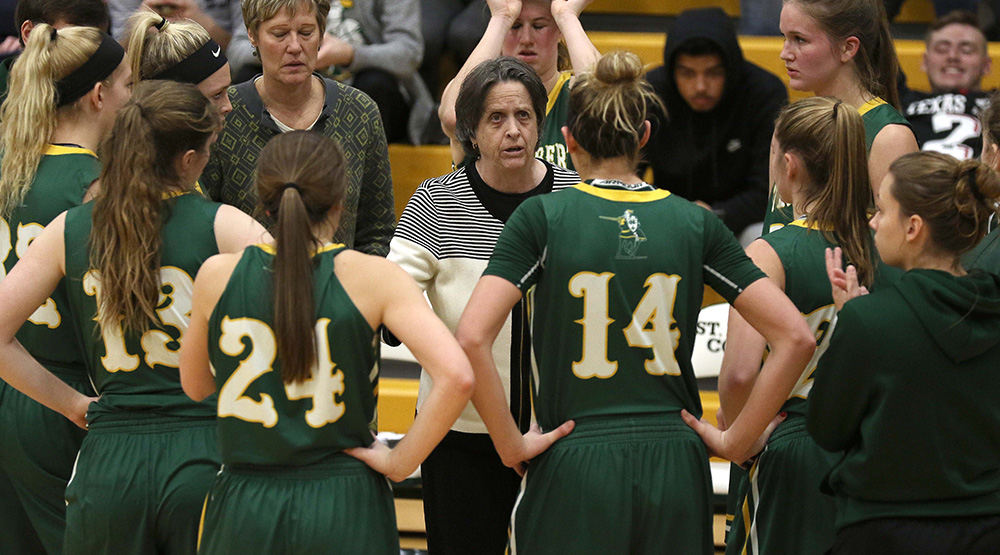 Connie Tilley with her St. Norbert women's basketball players during a 30-second timeout. (St. Norbert athletics photo)
