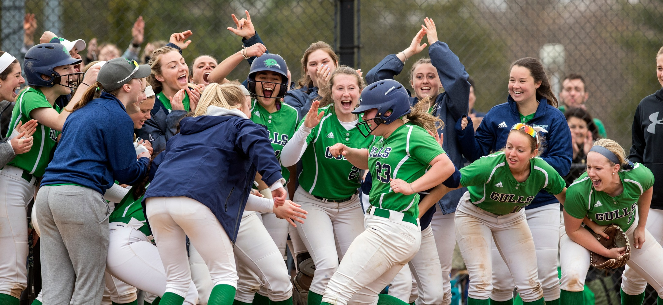 Hayley Arduini crosses home plate after a home run as her teammates celebrate around her.