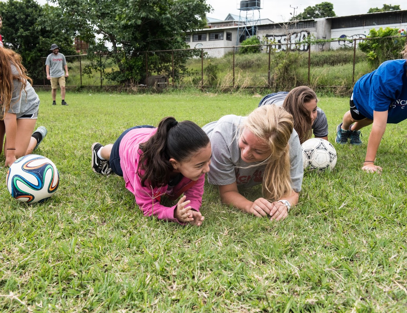 Photo of player exercising with little girl at soccer clinic