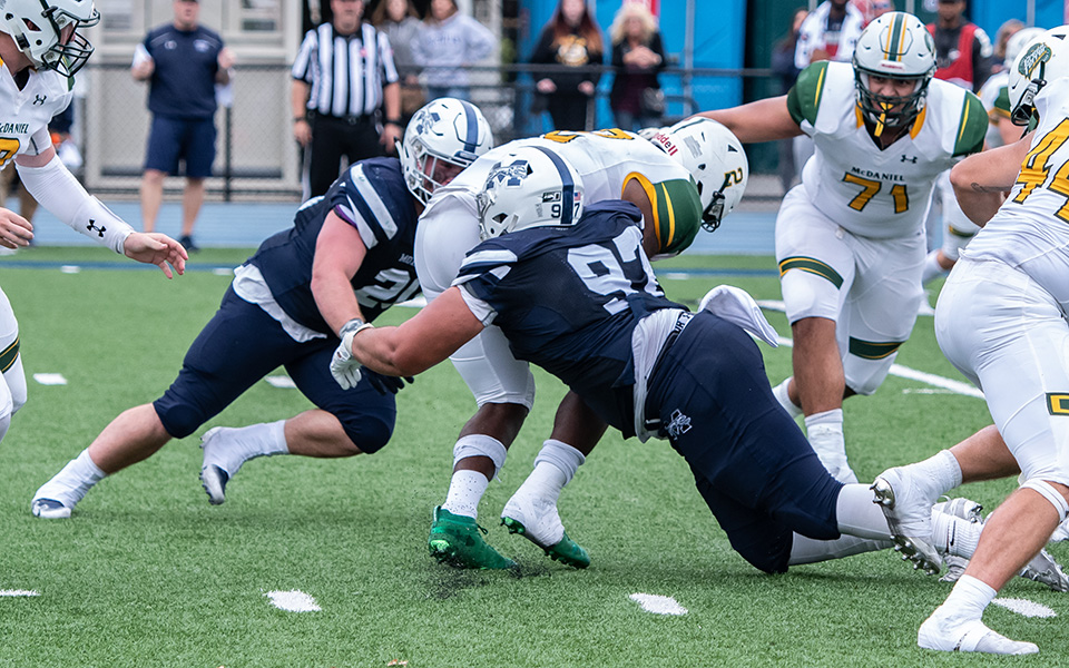 PJ Weierbach and Brady Hornbaker make a tackle in the backfield versus McDaniel College at Rocco Calvo Field.