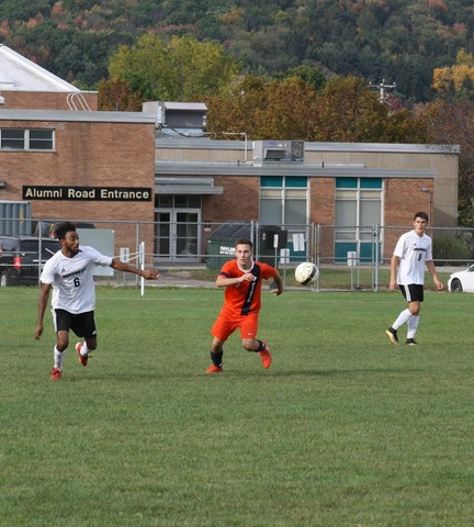 SUNY Broome men's soccer player and opponent chasing down ball