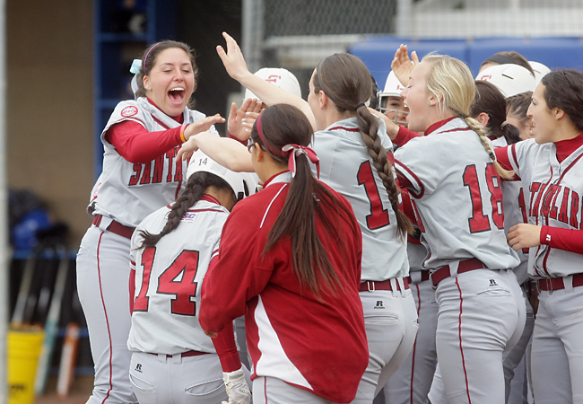 Briana Knight (#14) is greeted at home plate after her grand slam in Sunday's win over UCSB. (John Medina Photo)