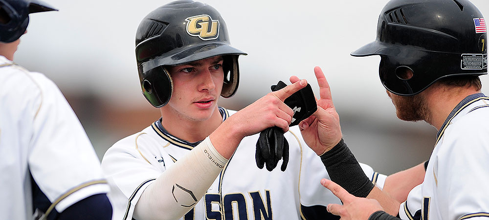 Gallaudet baseball player Jake Grindstaff is greeted by teammates after he scores a run. He is wearing a navy batting helmet with the initals GU on it.
