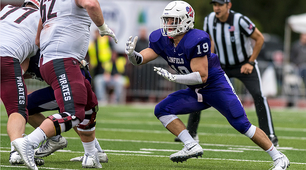 Patrick Pipitone heads toward a pair of Whitworth offensive linemen (Linfield athletics photo)