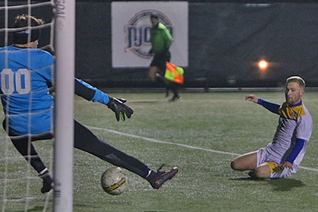 GCC Men's Soccer player shooting on goal in National Tournament