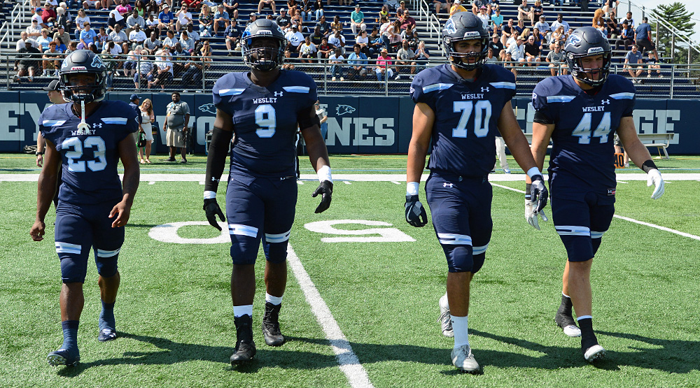 E.J. Lee, Vincent Ebron, Devin Miller and Andrew Eagle walking out for the coin toss for Wesley. (Wesley athletics photo)