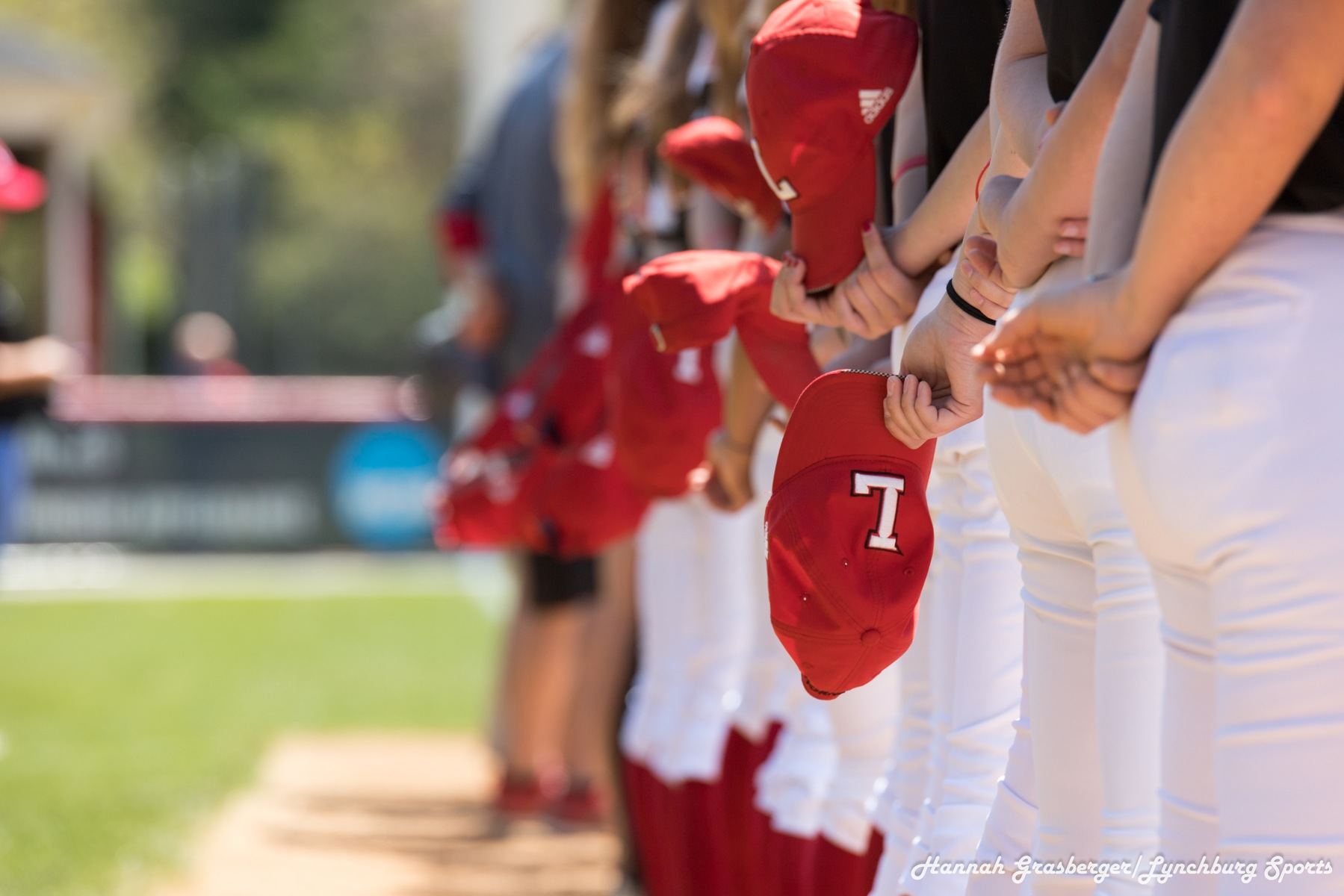 Artistic photo of Lynchburg players' hats looking down a line.