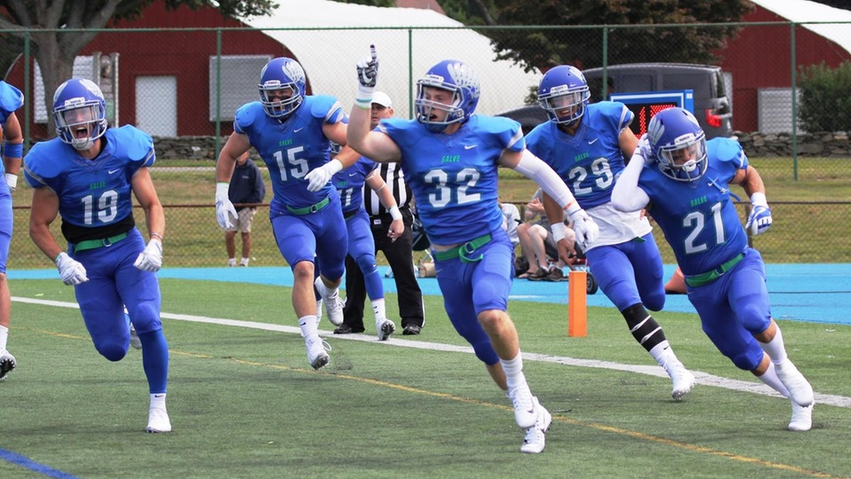 Charlie Connell (No. 32) celebrates his pick six with several Seahawk defenders in chase.