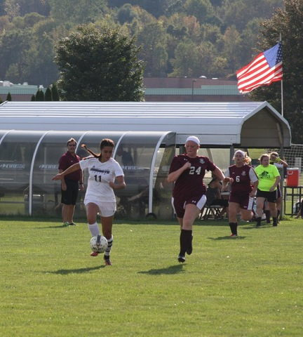SUNY Broome women's soccer player dribbling ball down sideline ahead of Jefferson Player