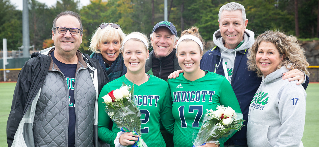 Cami Mollinare and Maggie O'Reilly pose with their families for a photo on Senior Day.