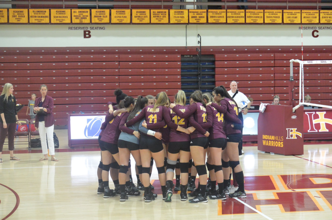 Volleyball Team huddling together on the court.