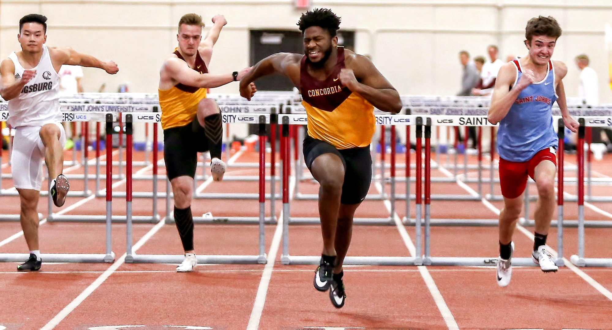 Willie Julkes stretches for the finish line in the prelims of the 60-meter hurdles at the MIAC Indoor Meet. He went on to set a school record in the finals of the event. (Photo courtesy of Nathan Lodermeier)