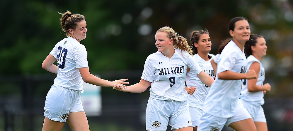 Hannah Neild and Brittany Mallach slap hands during a soccer game.